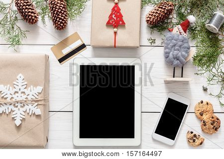 Christmas online shopping background. Tablet and mobile screens with copy space top view on white wood, present boxes, credit card and cookies. Internet commerce on winter holidays concept