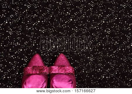 Fancy background. copy space. sparkling black. sparkling pink shoes. top view. festive.