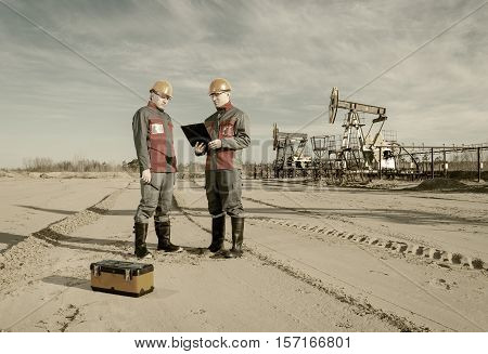 Two workers in the oilfield one holding the radio second showing papers. Pump jack and wellhead background. Oil and gas concept. Toned.