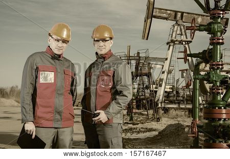 Workers in the oilfield one holding radio in his hand. Pump jack and wellhead background. Oil and gas concept. Toned.