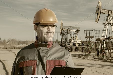 Worker wearing orange helmet in the oilfield. Pump jack and wellhead background. Oil and gas concept. Toned.