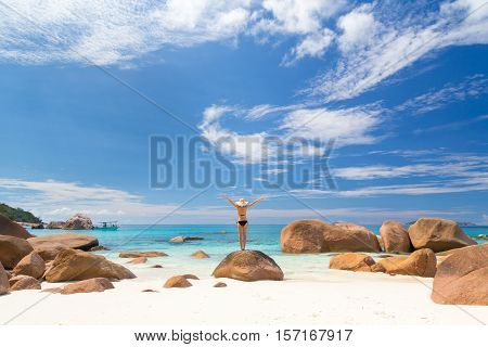 Woman, arms rised, wearing black bikini and beach hat, enjoying amazing view on Anse Lazio beach on Praslin Island, Seychelles. Summer vacations on picture perfect tropical beach concept. Copy space.