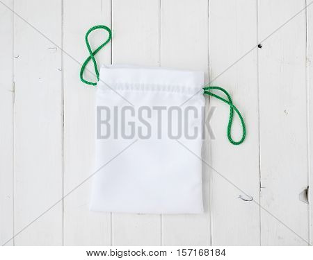 white little fabric gift sac with green ties on wooden table