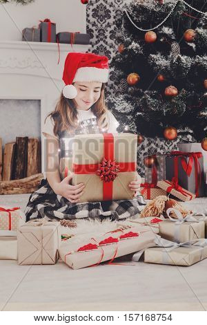 Beautiful happy girl in santa hat unwrap magic christmas present on holiday morning in beautiful room. Female child open Xmas gift near decorated fir tree and fireplace. Winter holidays concept