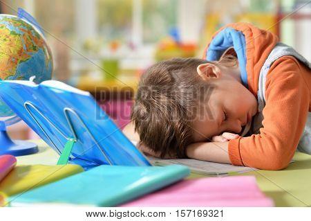 Tired little boy fell asleep while he was making his homework