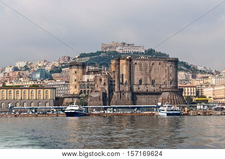 Naples Italy - October 7 2009: The Castel Sant'Elmo rises on the hill above the old town and Castel Nuovo welcomes the arriving travelers in port Naples Italy.