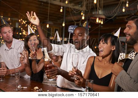 Friends uncorking champagne at a New Year party at a bar