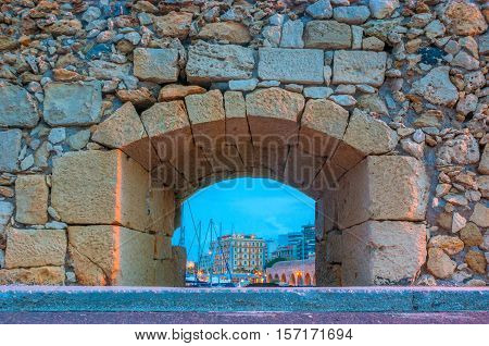 The loophole in the stone wall at Venetian fortress opens the view on evening port with sails of yachts and city buildings Heraklion Crete Greece.