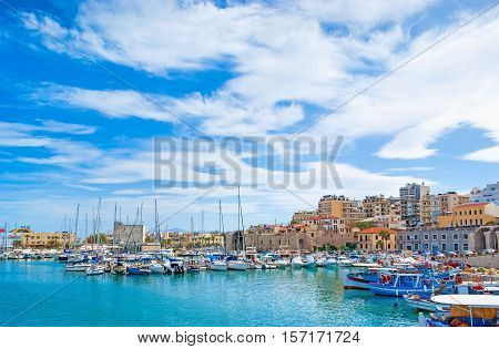 The walk along the harbor of Heraklion with ruins of Venetian era buildings and numerous yachts and boats in port Crete Greece.