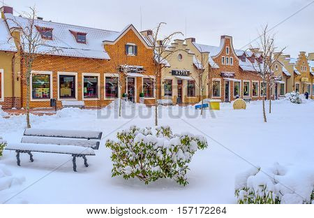 KIEV UKRAINE - NOVEMBER 11 2016: The snowy bench in park with the gambrel-roofed houses of Dutch Revival neighborhood on the background on November 11 in Kiev.