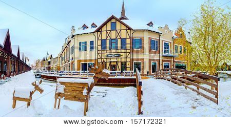 KIEV UKRAINE - NOVEMBER 11 2016: Panorama of the Dutch style shopping city with the sculptures of wooden moose at the snowy bank of the canal on November 11 in Kiev.
