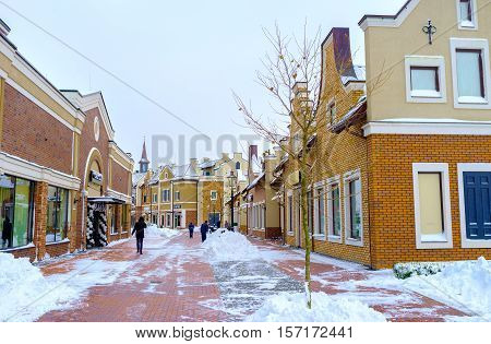 KIEV UKRAINE - NOVEMBER 11 2016: The snowy street in Dutch style shopping neighborhood with the gambrel roofs and curved eaves along the house on November 11 in Kiev.