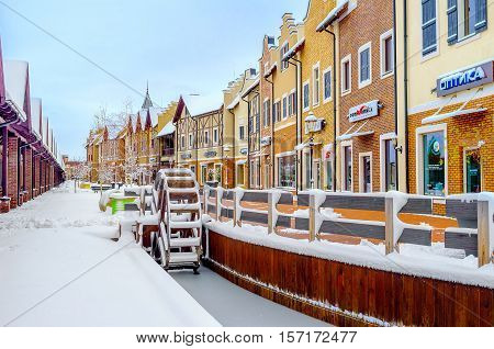 KIEV UKRAINE - NOVEMBER 11 2016: The wooden water wheel in a frozen canal in Dutch Revival style shopping city is covered with snow on November 11 in Kiev.