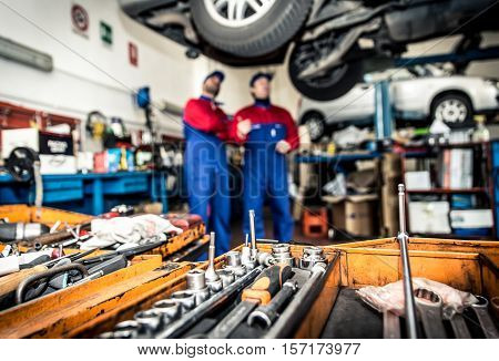Two mechanics working on a car in the garage