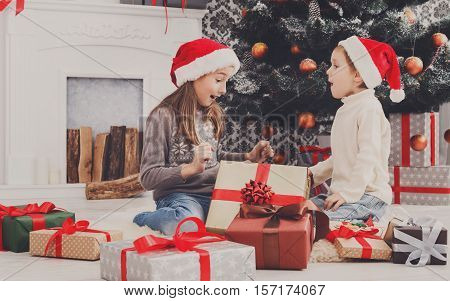 Cute happy excited children, boy and girl in santa hats unwrap christmas present box on holiday morning in beautiful room. Sister and brother open Xmas gifts near decorated tree and fireplace.