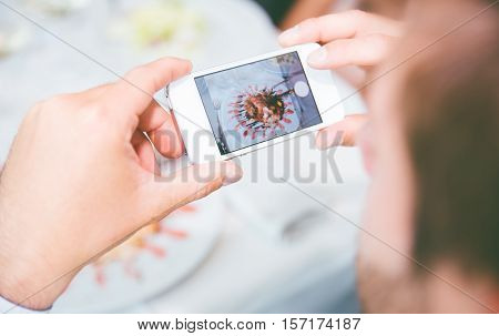 Man photographing food with smart phone. Food porn poster