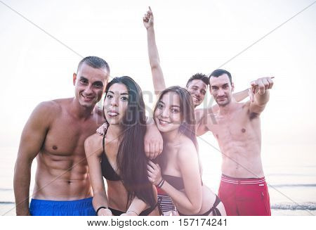 Friends taking selfie on the beach and sharing good mood