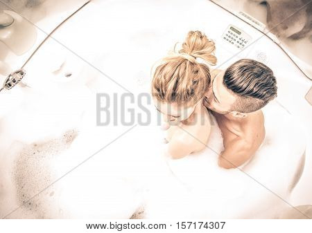 Couple in the jacuzzi. People taking bath with foam