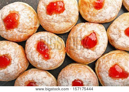 Close up view of tasty donuts with jam on dark background. Hanukkah celebration concept