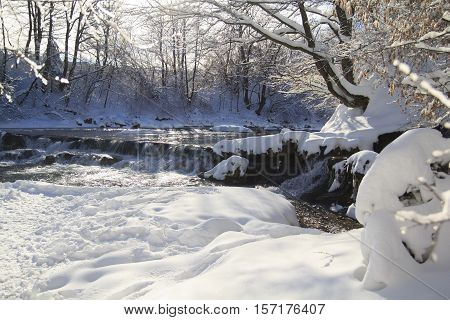 River with a little waterfall in winter forest with a lot of snow sparkling on sun