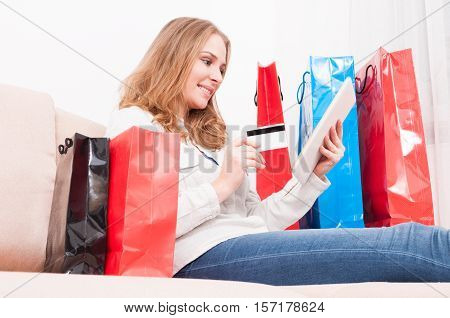 Lady Smiling And Shopping Online Holding Card With Bags Around