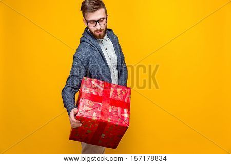 Studio shot of young man in casual outfit holding big red present box on orange background.