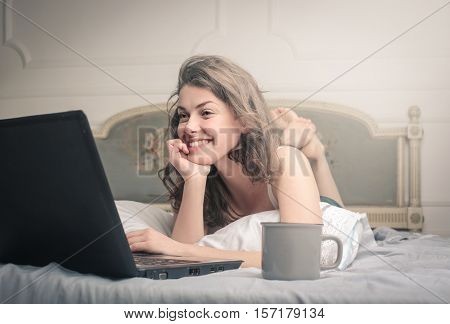 woman passing the time on her computer with a cup of coffe