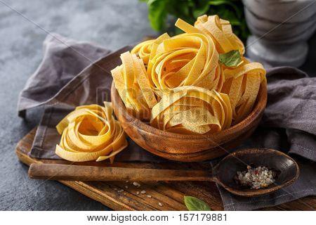 Freshly prepared fettuccine pasta on cutting board. Italian food.
