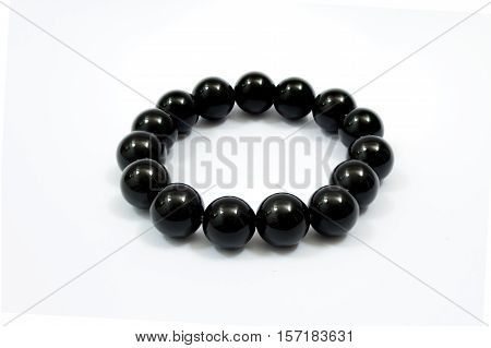 Black beads bracelet on white background. Simplified praying beads use for counting prayers or practicing mindfulness meditation.