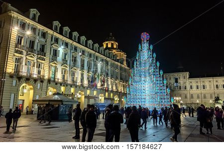 Turin Italy - December 31 2015 : Christmas Tree with tourists on new year's eve in Piazza Castello in Turin Italy. Piazza Castello is the main city square in Turin and is lined with museums theaters and cafes.