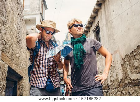Two tourists try to navigate with guidebook on unknown asian street