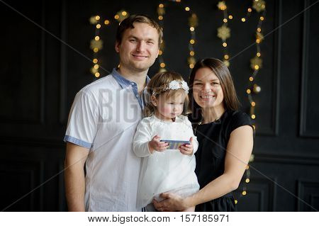 Young family is photographed in Christmas holiday. Chubby ruddy girl is elegantly dressed. In hands at the baby the smartphone. Parents laugh. Dark wall is decorated with garlands.