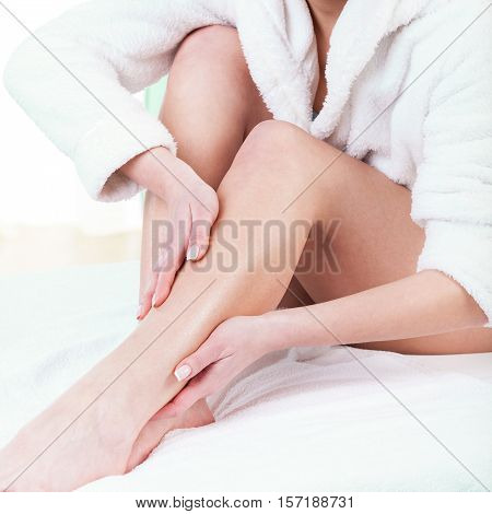Woman rubbing lotion on her legs after depilation