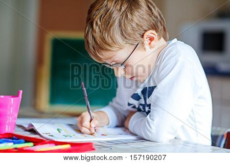 Portrait of cute happy school kid boy with glasses at home making homework. Little child writing with colorful pencils, indoors. Elementary school and education.