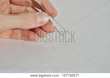 Isolated male hand holding silver tweezers (cosmetic pincer used for face cultivation)