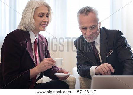 Discussing the project. Smiling bearded aged businessman looking and pointing on the laptop and sitting in the hotel while working on the project with his colleague and expressing interest