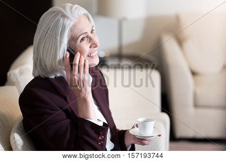 Delightful conversation. Delighted cheerful aged businesswoman smiling and drinking a coffee while sitting in the hotel and talking on the hone