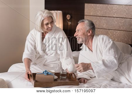 Breakfast tray. Delighted smiling aged woman sitting on the bed and holding the breakfast tray while having a breakfast with her husband and expressing happiness