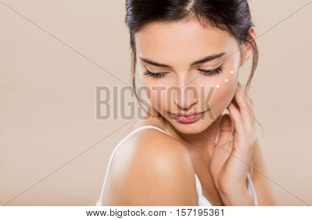 Young woman looking down with face moisturizer near eyes. Beautiful woman applying face lotion on cheek. Beautiful intimate girl with perfect and healthy skin feeling shy isolated on warm background.