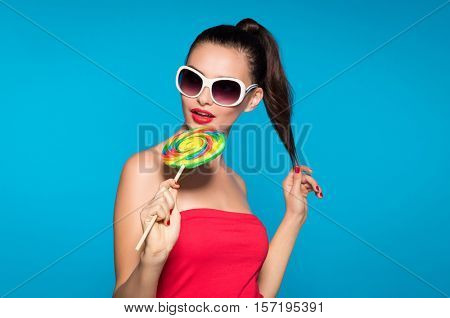 Young beautiful woman holding lollipop isolated on blue background. Happy girl wearing red top and sunglasses eating multi colored candy. Sexy joyful and cheerful woman eating lollypop having fun.