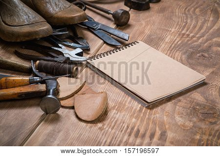 Set of tools notebook for shoemaker on the wooden background.