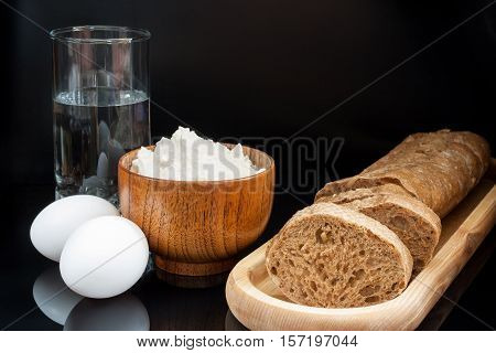 Ingredients for baking bread: flour, eggs, glass of water with fresh sliced baguette on black background.