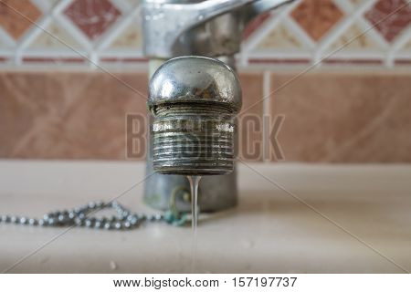 Water tap close-up with limescale soiled calcified faucet water flowing