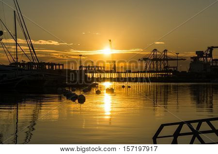 sunrise at the Valencia harbor, some clouds sun rises between docked sailboats and cargo port cranes orange red colors in the sky and water reflection