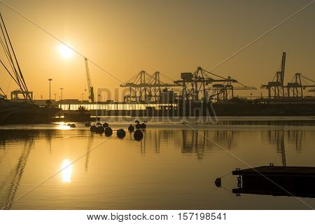 sunrise at the Valencia harbor, the sun rises between docked sailboats and cargo port cranes, orange colors in the sky and water reflection