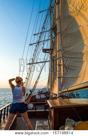 Santorini Greece - October 13 2012: A young lady taking a photograph from the deck of a Brigantine in navigation in the Caldera sea area at nightfall