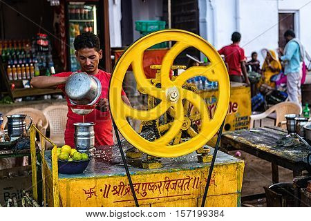 Pushkar, Rajasthan, INDIA - November 11, 2016: Young Indian man making lemon juice with wheeled juicer at Pushkar camel fair