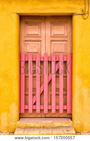 Multicolored adobe building and wooden door with picket gate in Cozumel Mexico