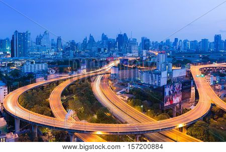 Long exposure highway road curved intersection in Bangkok city downtown at twilight