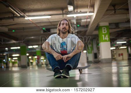 Skateboarder Sitting On His Skateboard In The Underground Garage